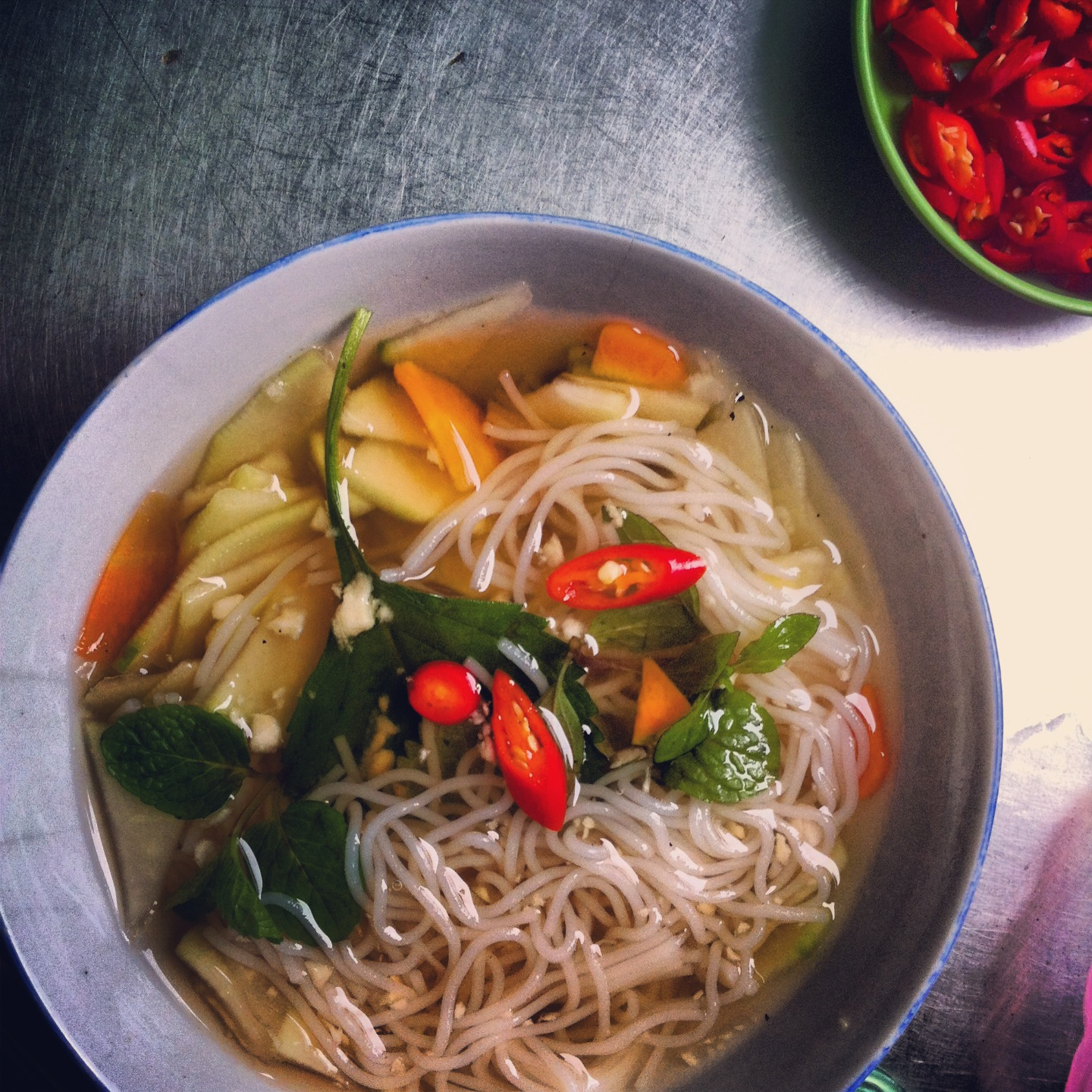 bowl of soup with noodles and herbs