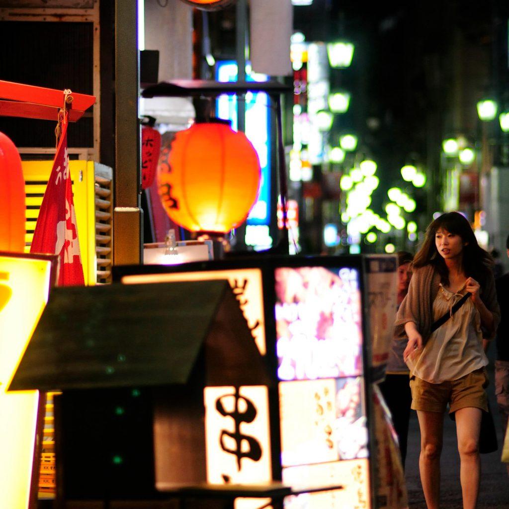 woman walking down tokyo street at night