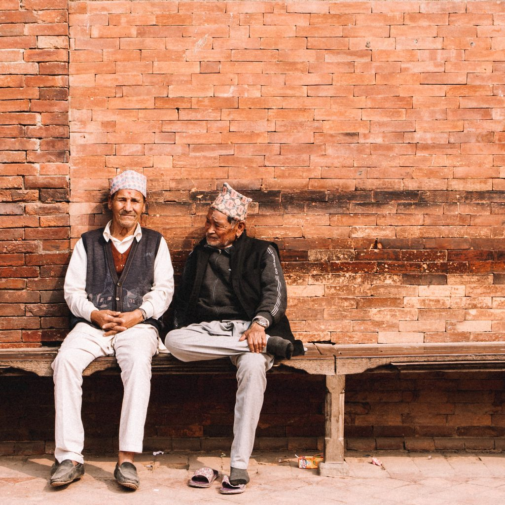 Two old men wearing traditional Nepali Dhaka Topi hats pass time by chatting animatedly in Kathmandu Patan Durbar Square. At squares across the city #localsknow that these are the best places to catch up with their friends and family, to reconnect with Nepal's history, and people-watch the vibrant sites in action.