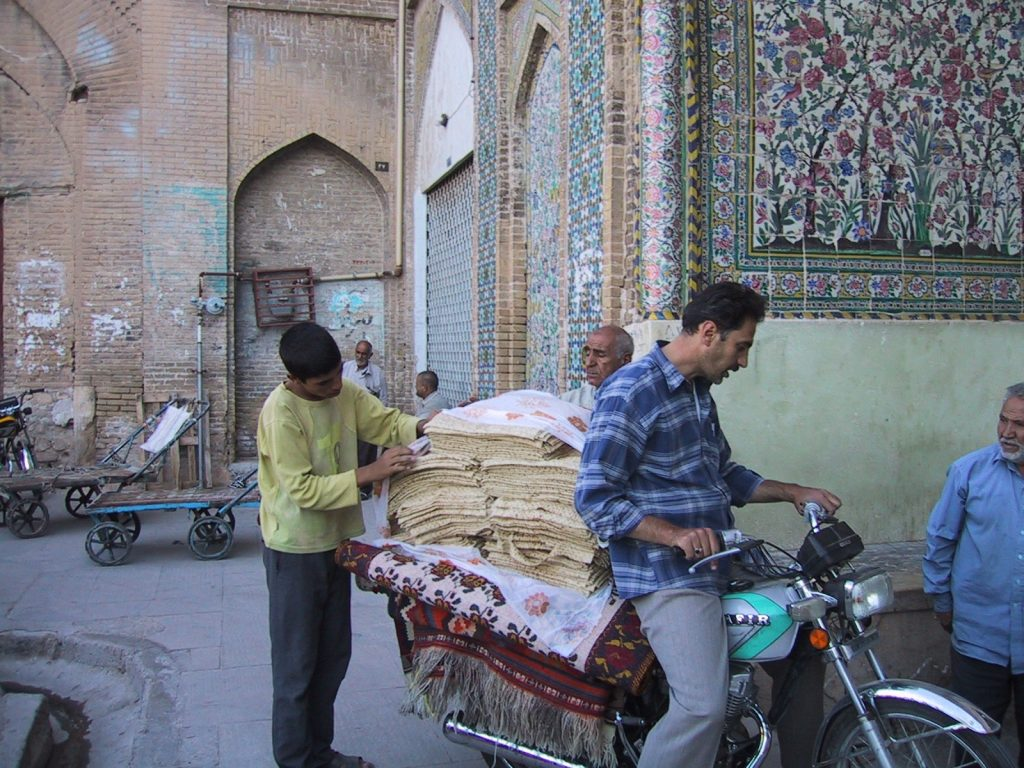 Men delivering goods on a motorcycle in Iran