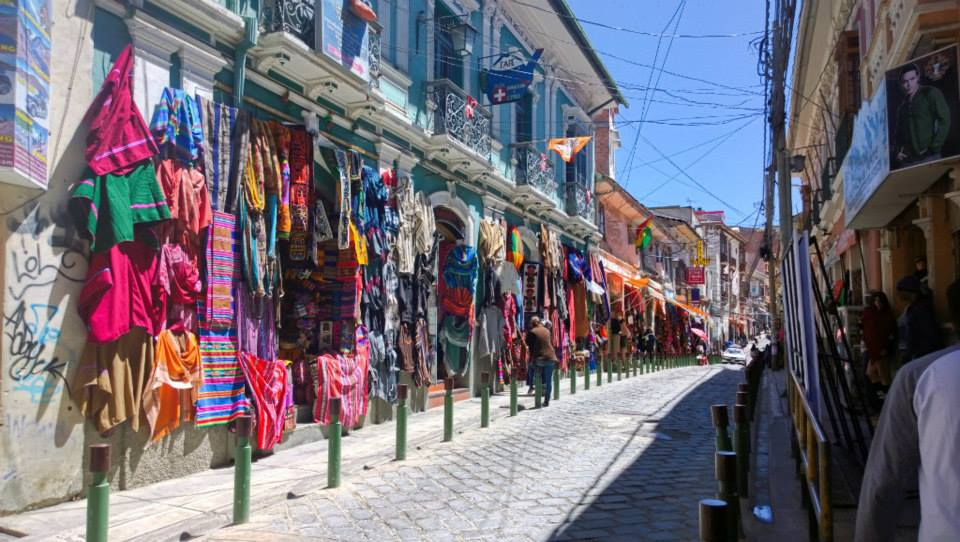 street in La Paz with coloured textiles hanging along the storefronts