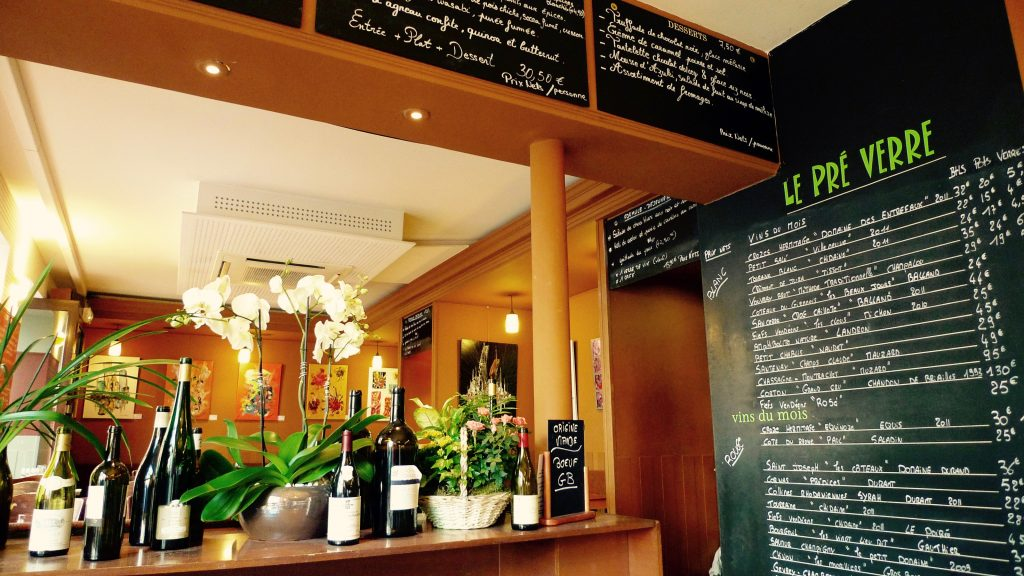 Flowers and wine bottles on a counter in a Paris bistro