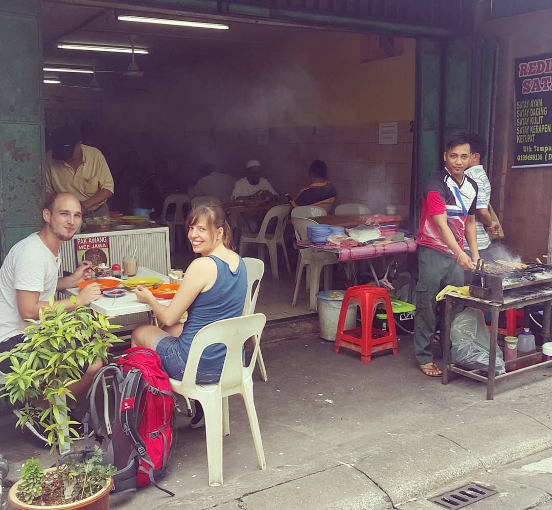 travellers sitting at a food stall in Kuching