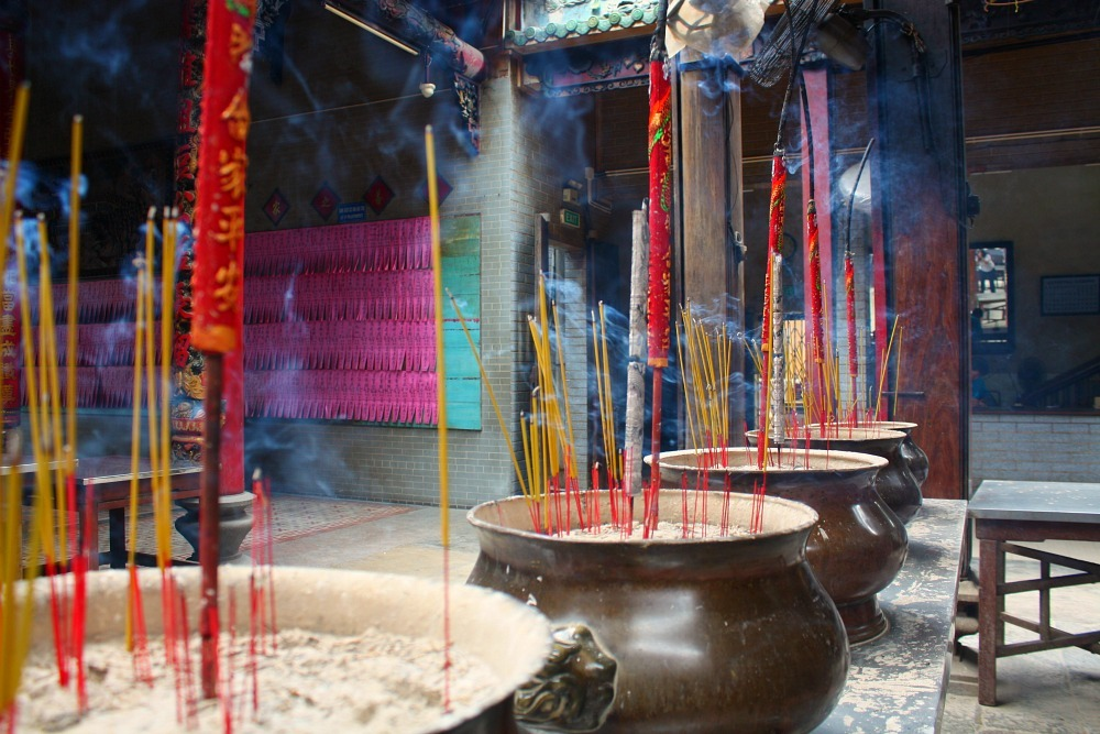 sticks of incense burning in a pagoda in HCMC