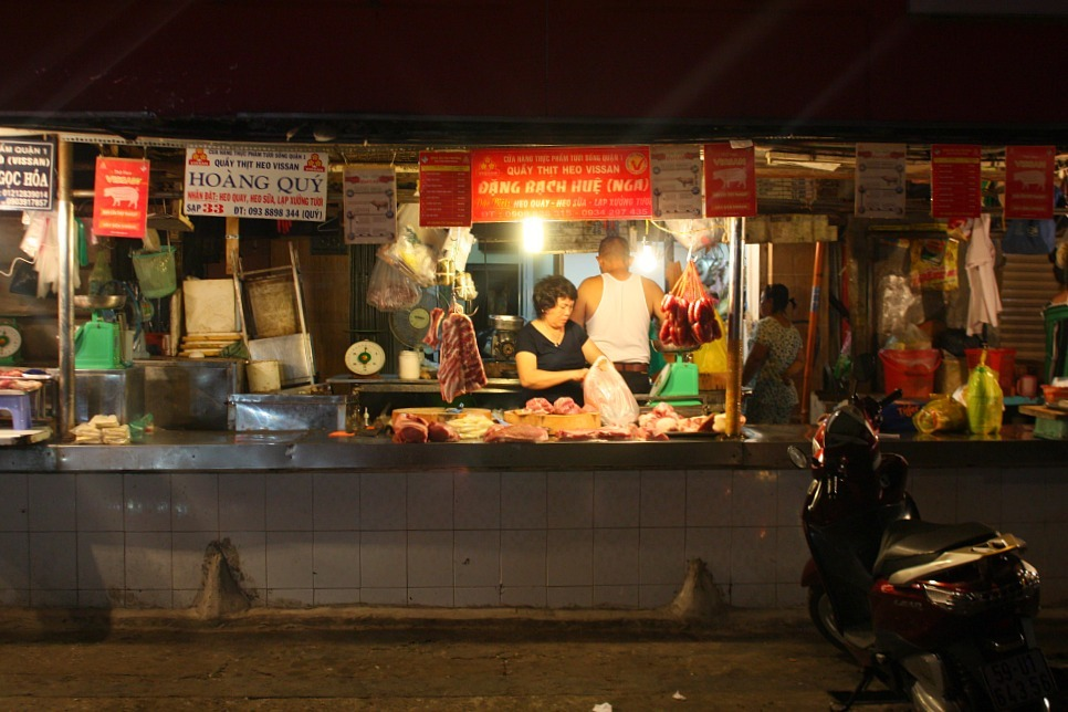 Vendor prepping food at a night market in HCMC