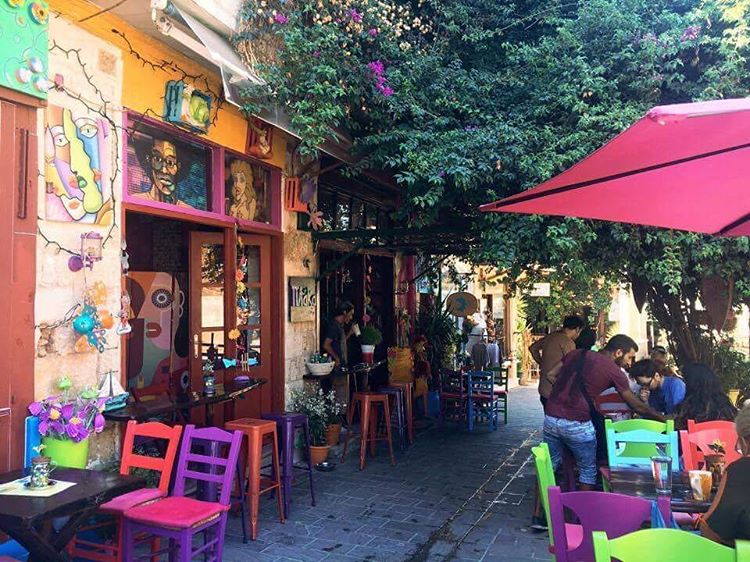 colourful laneway in Chania with chairs outside a cafe