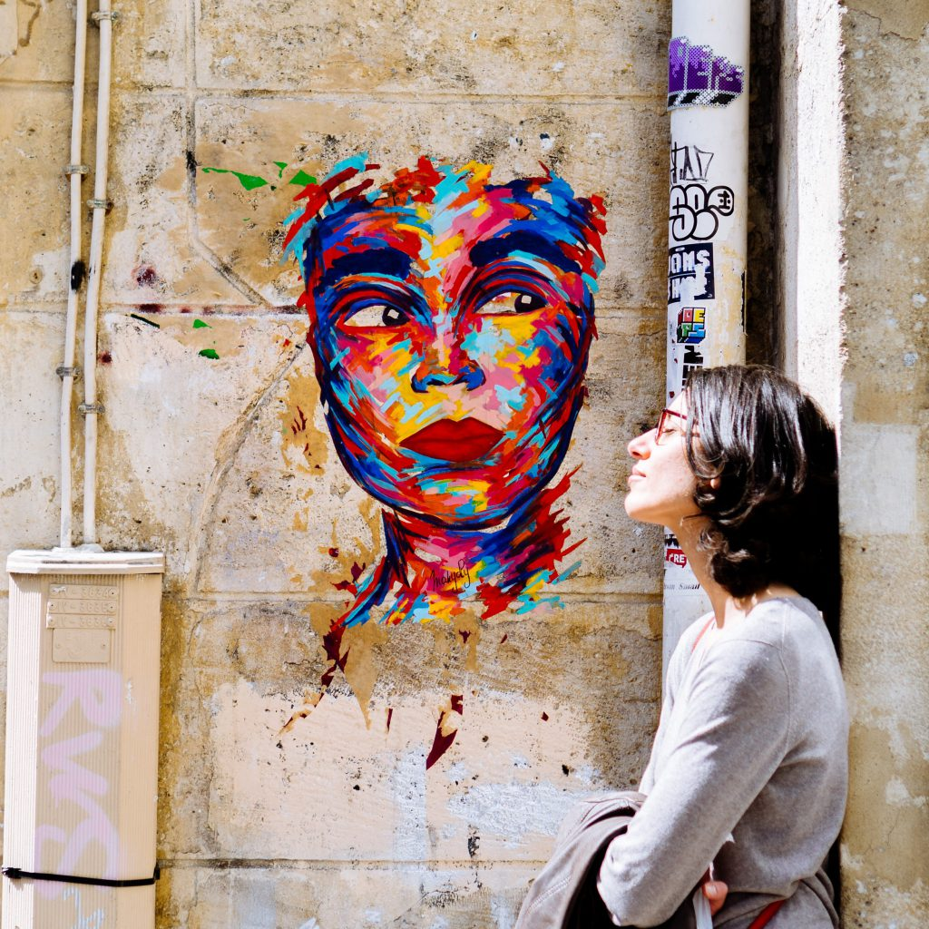 woman leaning against a wall with a painting of a face in Paris