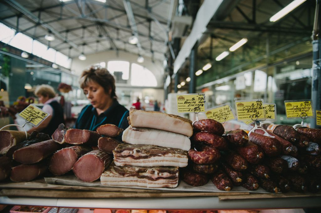 women at a butcher stall at a market in Lithuania