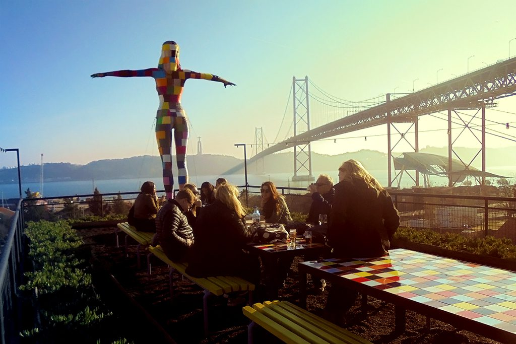 people gathered at tables on the waterfront in Lisbon, in front of an art sculpture