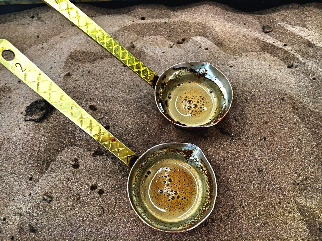 traditional Greek coffee being brewed over sand