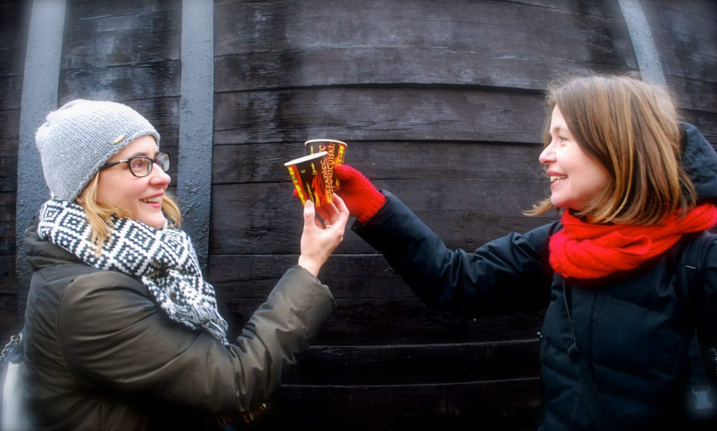 two women cheersing cups of mulled wine in Krakow