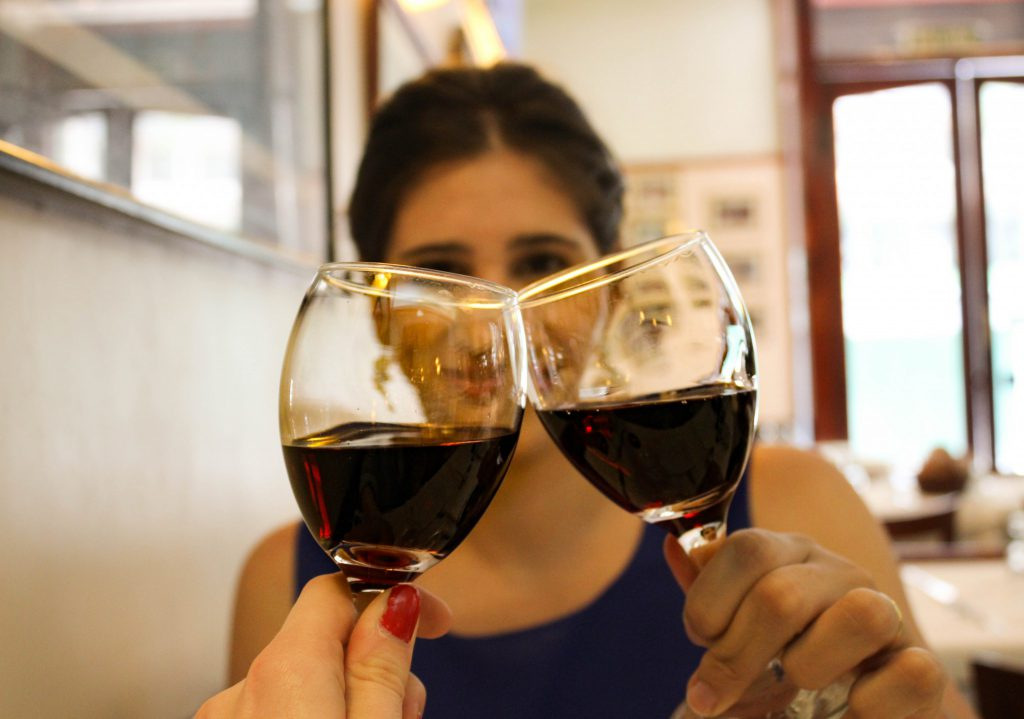 local woman and traveller cheersing with wine glasses