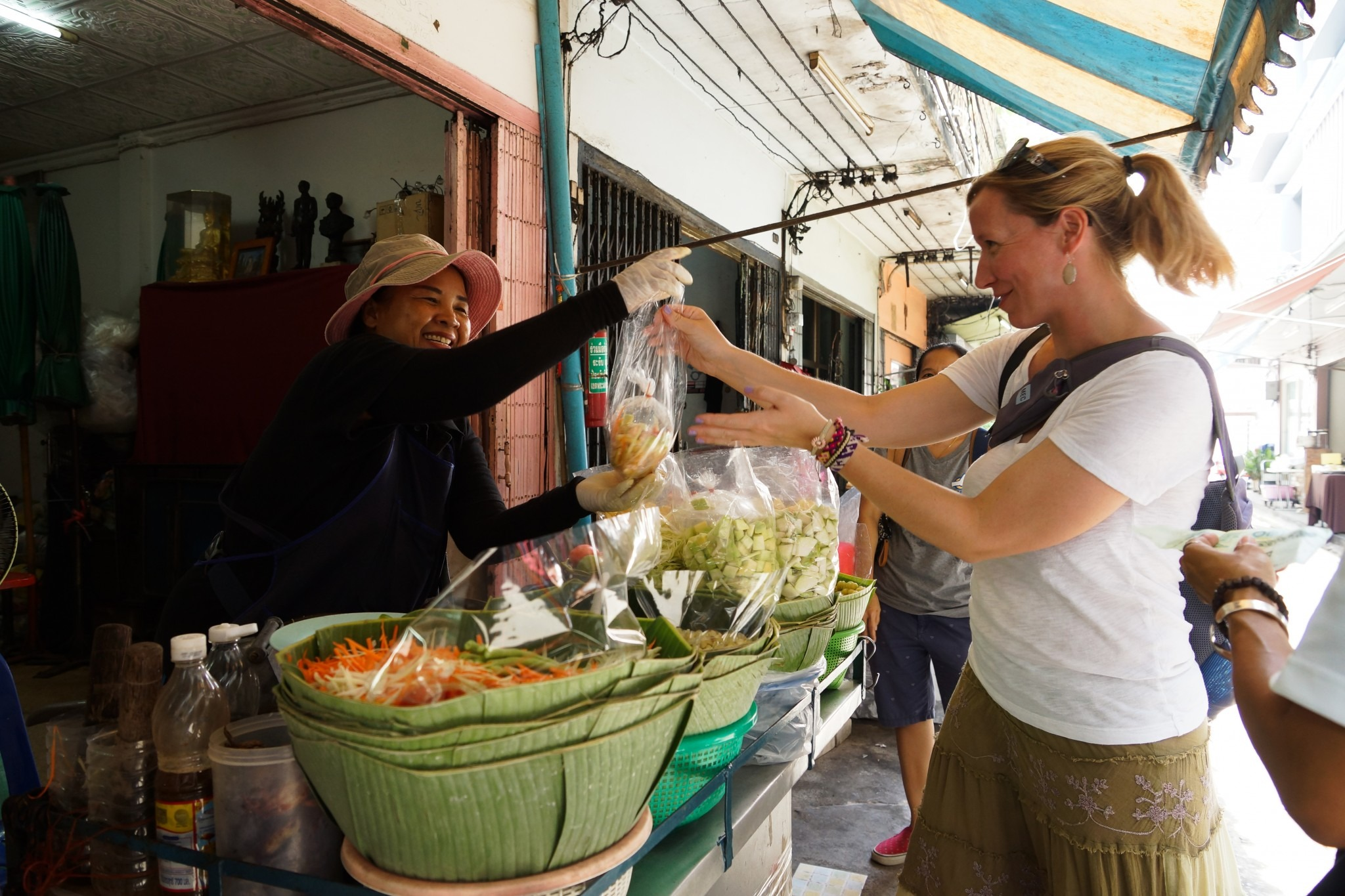 woman selling a bag of takeaway fruit salad