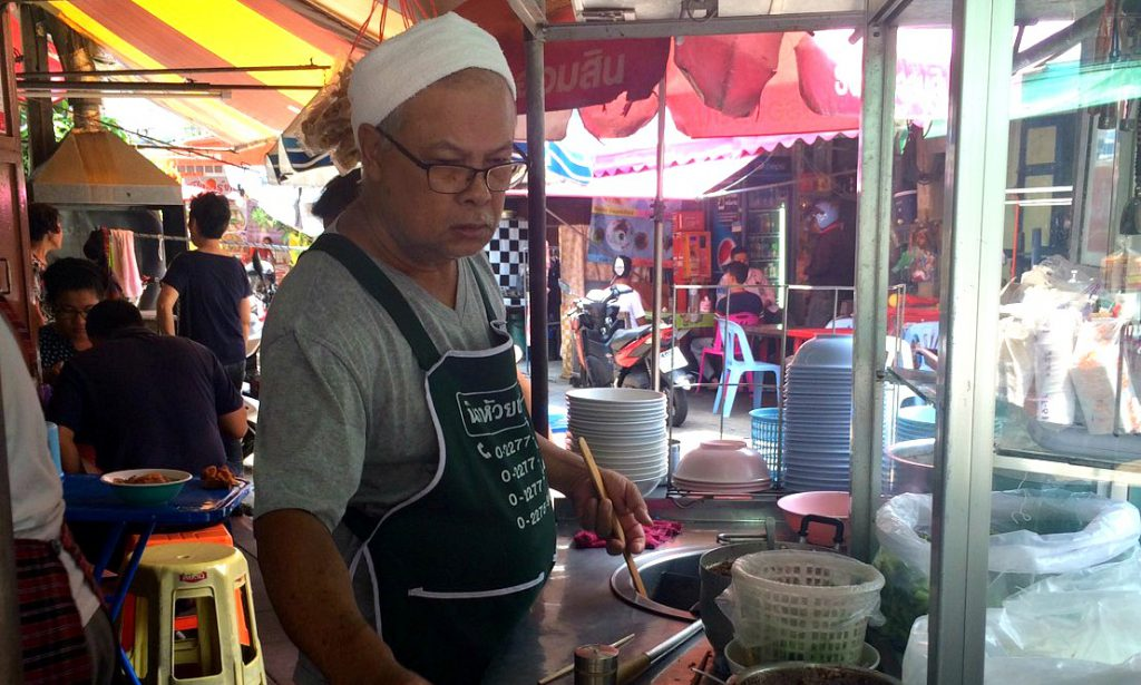 man cooking at a street stall in Bangkok