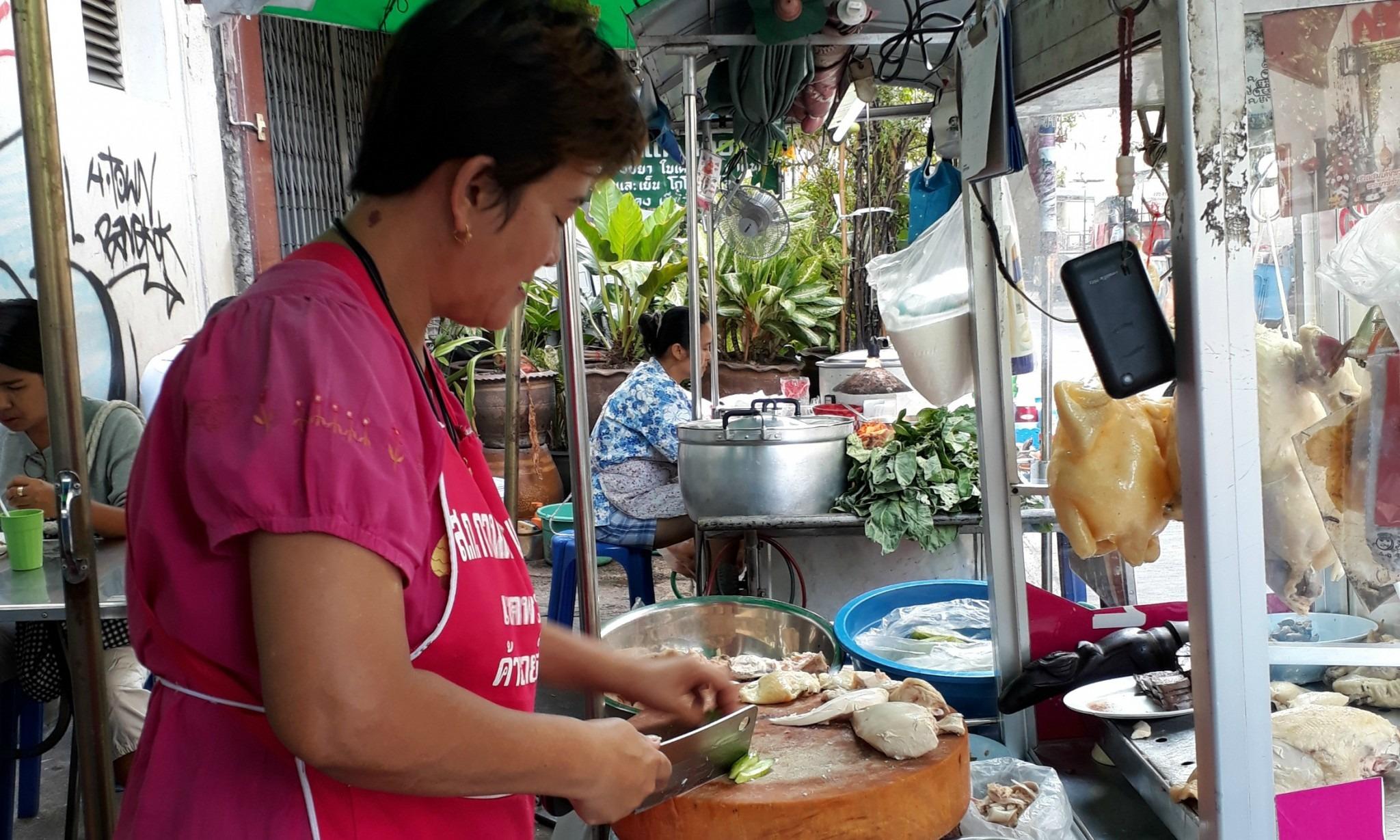 woman cooking at a street stall in Bangkok