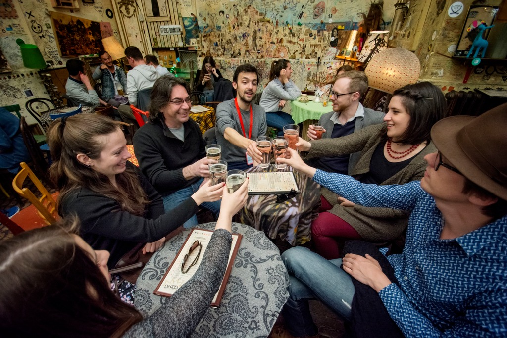 travellers cheers-ing drinks in a bar in Budapest