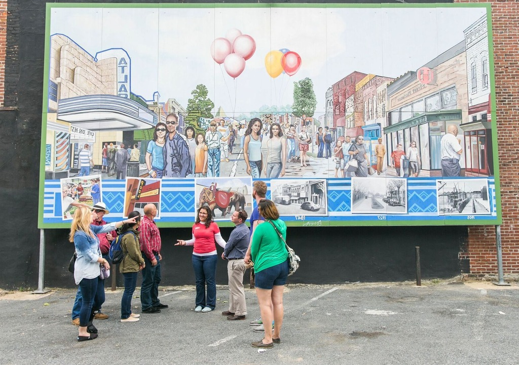 travellers and guide in front of a mural in Washington, DC