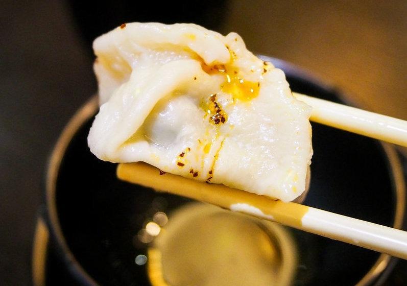 chopsticks holding a dumpling