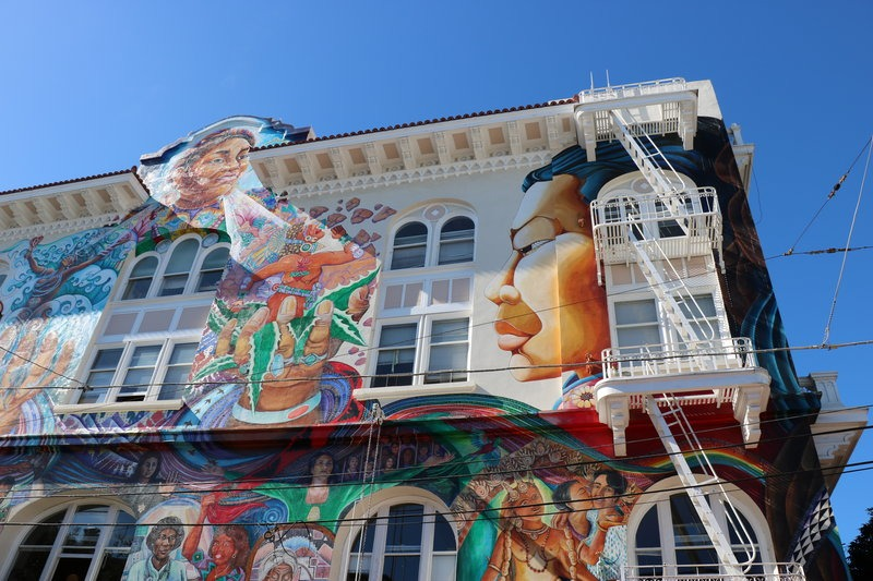 white building with a mural of women along the side