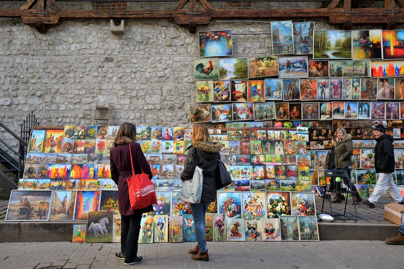 traveller and tour guide looking at art on display outside in Krakow