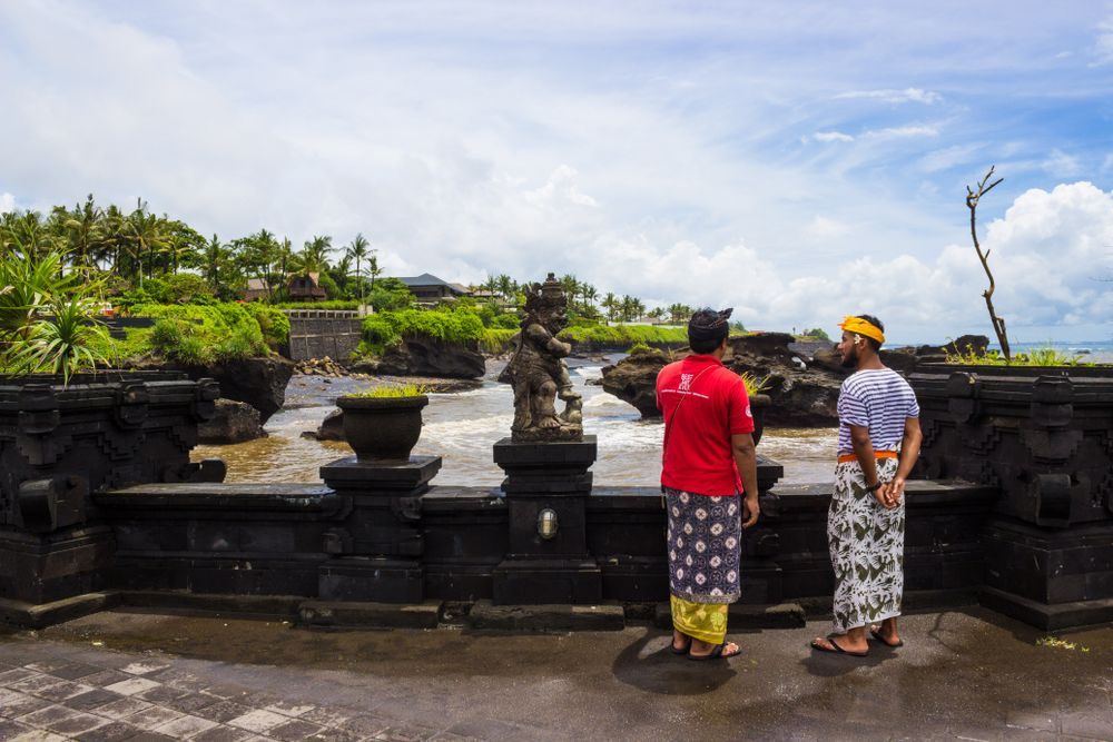 Balinese tour guide showing a temple to a traveller