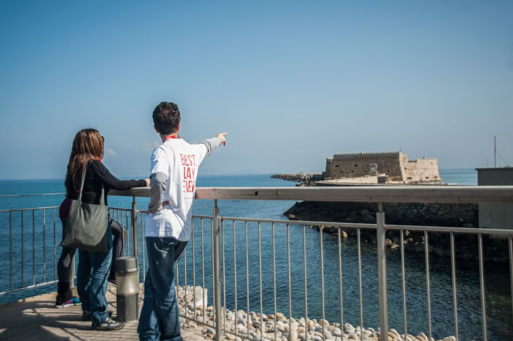 tour guide pointing at a fort across the water