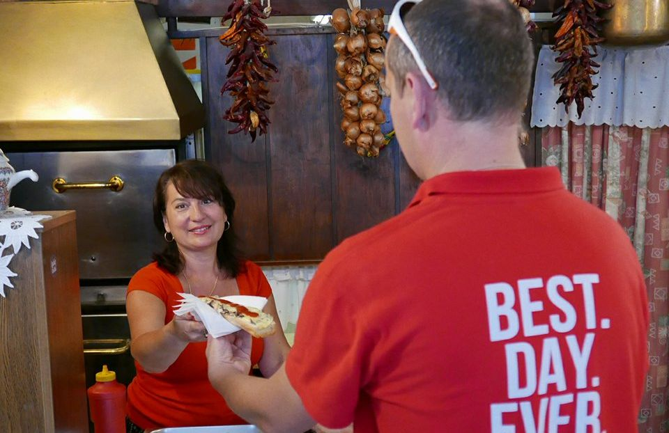 woman selling open-faced sandwich to a customer