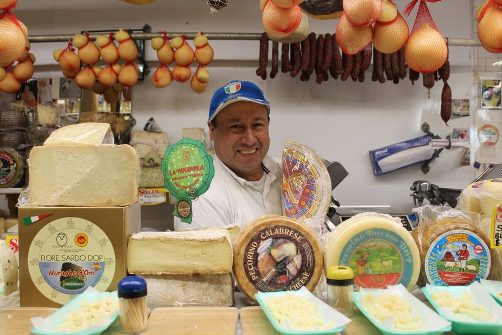 shopkeeper behind the counter in a cheese store