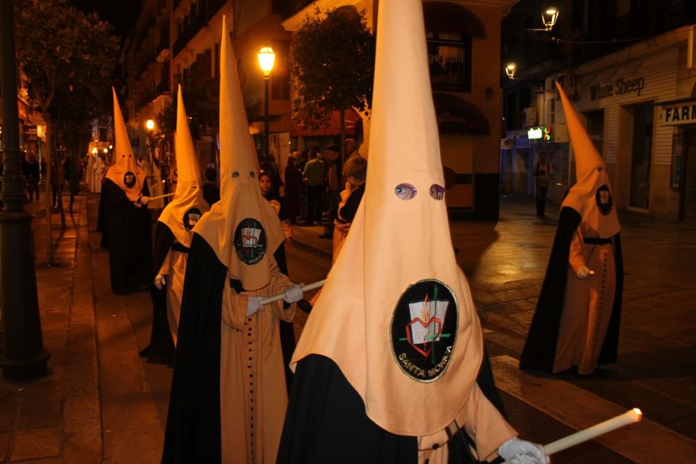 hooded church figures walking in procession for Holy Week