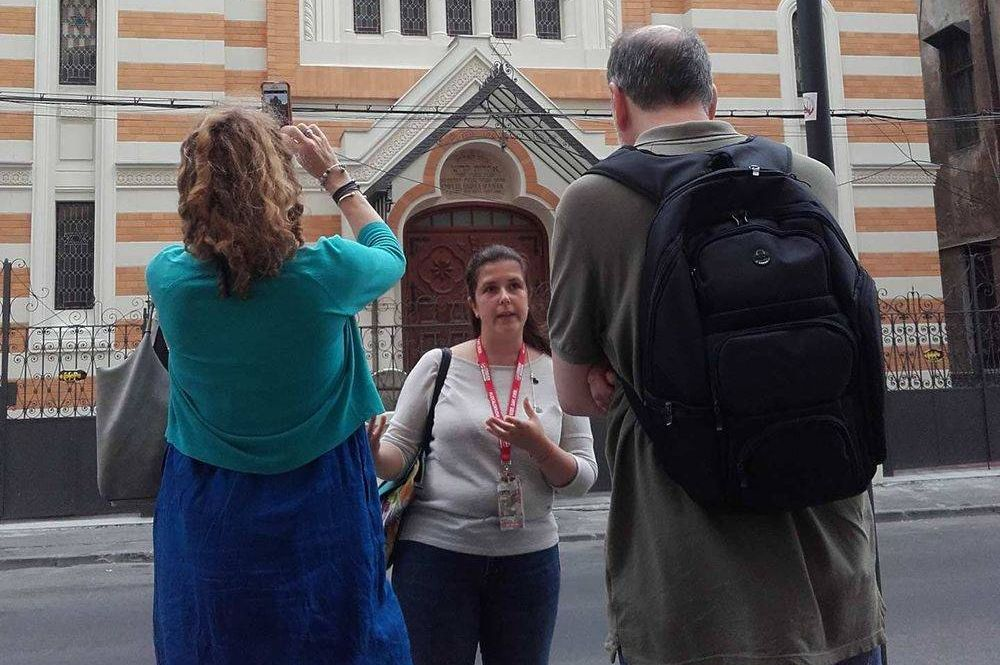 tour guide with travellers in front of a church in Bucharest