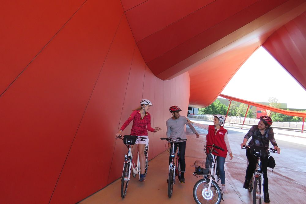 travellers on bikes under a red structure at the Canberra museum
