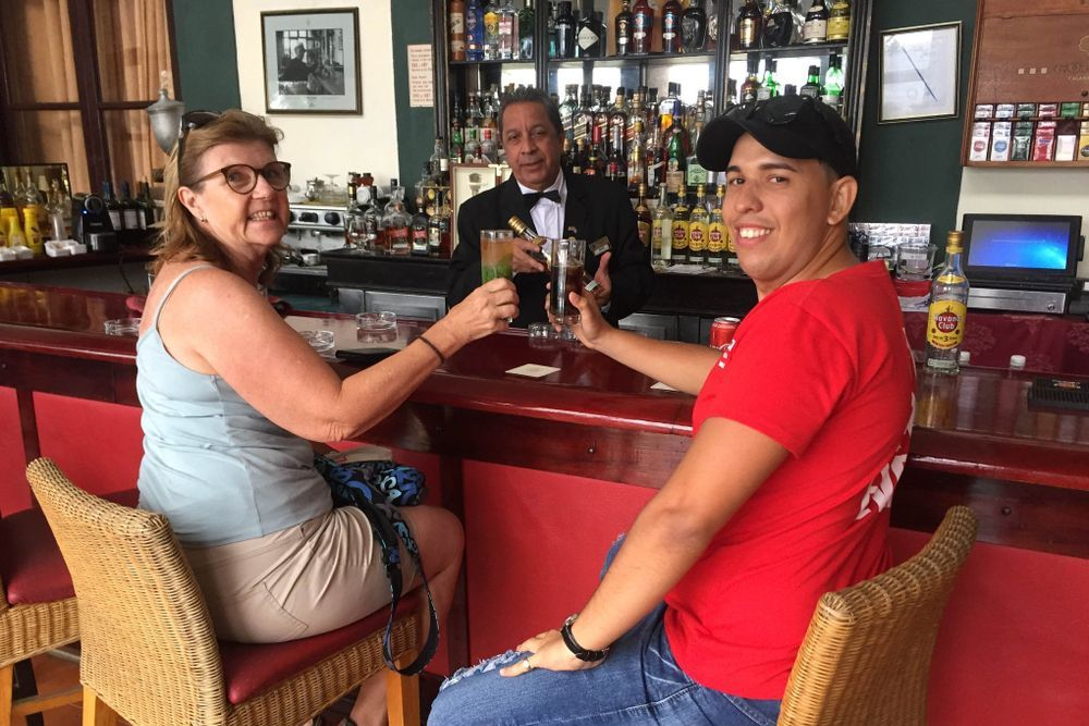 traveller and tour guide sitting at a bar with drinks