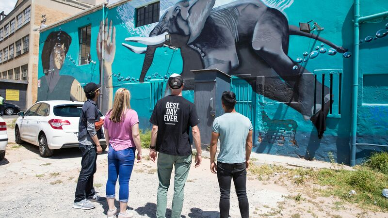 Urban Adventures guide showing travellers murals at Salt River, Cape Town