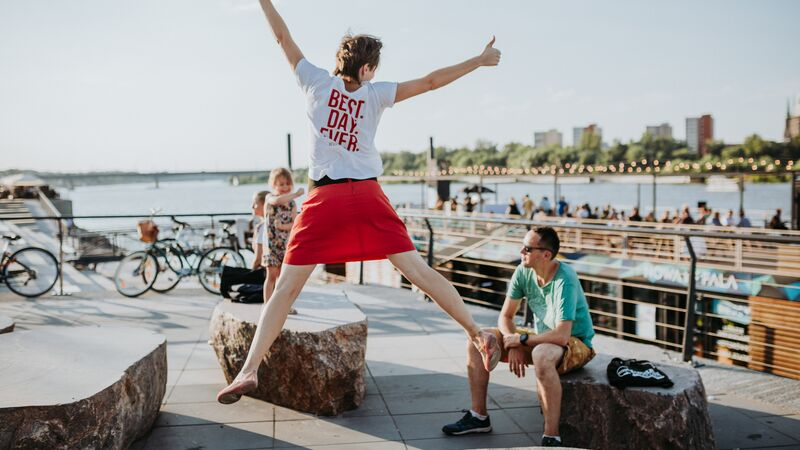 Urban Adventures guide jumping for joy by the river in Warsaw