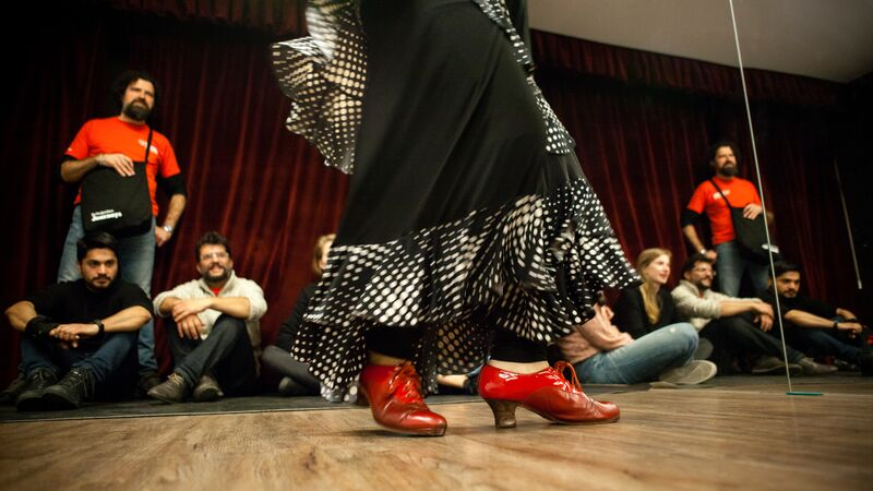 Close-up of flamenco dancer's shoes, with tour participants in the background