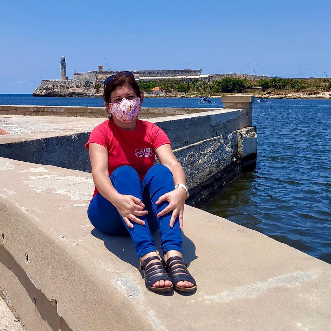 tour guide sitting by the water, wearing a mask